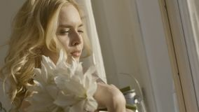 Young blonde woman with flowers in her hands in the sun. Action. Young beautiful woman in sunlight at home with flowers royalty free stock photos