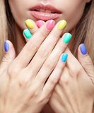 Young blonde woman with fun  varicoloured finger nails manicure Royalty Free Stock Photography