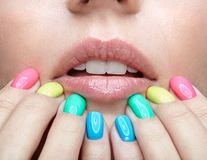Young blonde woman with fun  varicoloured finger nails manicure. Royalty Free Stock Photography