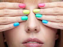 Young blonde woman with fun  varicoloured finger nails manicure. Stock Photography