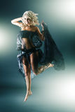 Young blonde woman in funky dress jumping Royalty Free Stock Photos