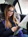 Young blonde woman in glasses exploring road map on back seat in car. Snow blizzard and rain outside. Royalty Free Stock Photos