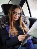 Young blonde woman in glasses exploring road map on back seat in car. Snow blizzard and rain outside. Royalty Free Stock Image