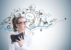 Young blonde woman in glasses writing, planning Stock Images