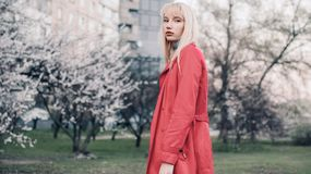 Young blonde woman goes for walk in spring garden on background of blossoming trees. Royalty Free Stock Images