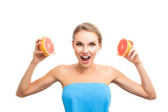 Young blonde woman with grapefruit Royalty Free Stock Image