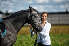 Young blonde woman with a gray horse on nature Royalty Free Stock Photography