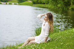 Young blonde woman on green meadow Stock Photography