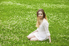 Young blonde woman on green meadow Royalty Free Stock Images
