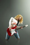 young blonde woman with a guitar sings a rock song Royalty Free Stock Photos