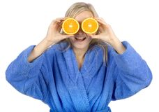 Young blonde woman with halfs of orange Stock Photos