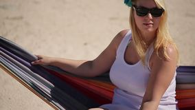 Young blonde woman in hammock. On the beach stock footage