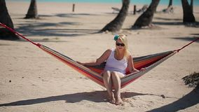 Young blonde woman in hammock. On the beach stock video