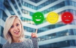 Winged pound. Young blonde woman, with a happy emotion give feedback, choosing smiling emoticon rating. Excellent customer service concept Royalty Free Stock Photo