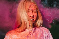 Young blonde woman having fun with colorful dry paint at the park. Concept for festival Holi. Young blonde model having fun with colorful dry paint at the park stock photos