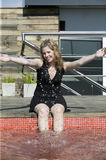 Young blonde woman having fun with water. At the pool Royalty Free Stock Photo