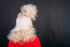 Young blonde woman head from back side black background. Young blonde head woman in red dress from back side black background Stock Photography