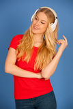 Young blonde woman with headphones  listens to the music over bl Royalty Free Stock Image