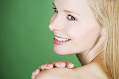 A young blonde woman with her hand on her shoulder, smiling Royalty Free Stock Photo