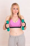 Young blonde woman with her weights Royalty Free Stock Image