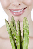 A young blonde woman holding a bunch of asparagus, close-up Royalty Free Stock Photo