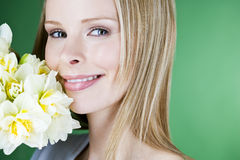 A young blonde woman holding a bunch of daffodils, smiling Royalty Free Stock Image