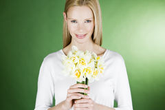 A young blonde woman holding a bunch of daffodils, smiling Stock Photos
