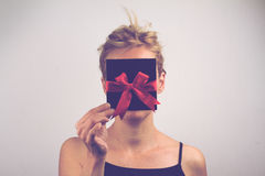 Young blonde woman holding a card with ribbon in front of her fa Royalty Free Stock Images