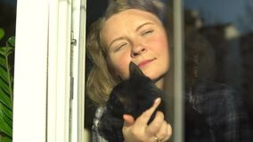 Young blonde woman holding a cat and looking out of the window with a smile. Staying home during Corona virus quarantine
