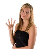 Young blonde woman holding four fingers. Portrait of a beautiful young blonde woman in a black dress holding up four fingers isolated on a white background Stock Image