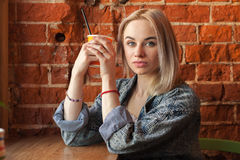 Young blonde woman holding orange paper cup with cocktail straw sitting near window against red brick wall at the cafe quizzically Royalty Free Stock Images