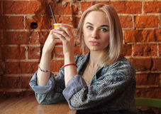Young blonde woman holding orange paper cup with cocktail straw sitting near window against red brick wall at the cafe quizzically Royalty Free Stock Photography