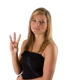Young blonde woman holding three fingers. Portrait of a beautiful young blonde woman in a black dress holding up three fingers isolated on a white background Royalty Free Stock Image
