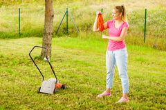 Woman rolling up extension cord. Young blonde woman holding work tool rolling up cable garden extension cord royalty free stock images
