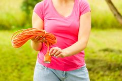 Woman rolling up extension cord. Young blonde woman holding work tool rolling up cable garden extension cord royalty free stock photo
