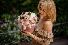 Free Young Blonde Woman Holds Cute Round Box With Flowers Decorated With Soft Toy Royalty Free Stock Images - 188558879