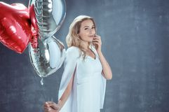 Young blonde woman holds heart-shaped balloons. And smiles royalty free stock images