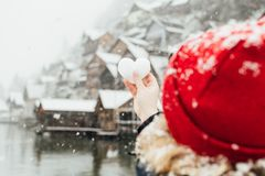 Free Young Blonde Woman In Red Hat Holding Heart Shaped Snow Ball In Front Of The Old Village Of Hallstatt, Austria Stock Photography - 136816212