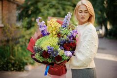 Free Young Blonde Woman In White Sweater Holds Bouquet With Different Bright Flowers Royalty Free Stock Photo - 189844085