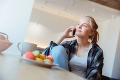 Young woman at home in the kitchen drinking tea phone call stock photo