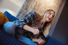 Young woman at home in the living room playing excited stock images