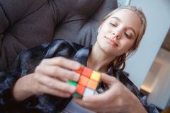 Young woman at home lying in hammock solving rubik`s cube. Young blonde woman indoors lying in hammock close-up solving rubik`s cube puzzle smiling royalty free stock image