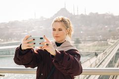 Young blonde woman in jacket makes selfie against background of glass window. stock photos