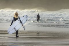 Young blonde woman joins boyfreind surfing, Fistral Beach, Newquay, Cornwall stock photos