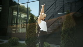 Young blonde woman kneads wakes up enjoys the rays of the sun against the background of a glass wall stock video footage