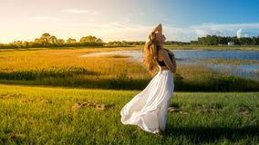 Young blonde woman in landscape with peaceful face during sunset skirt hair blown by the wind. Yellow soft light royalty free stock photography