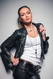 Young blonde woman in leather clothes pulling her collar. On poses in studio Royalty Free Stock Image