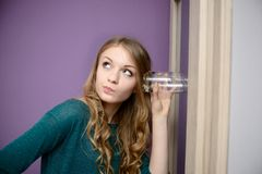 Young blonde woman listening in to a conversation with a glass Stock Photos