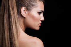 Young blonde woman with long hair in ponytail profile studio Royalty Free Stock Photography