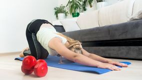 Young blonde woman with long hair stretching on fitness mat at home. Blonde woman with long hair stretching on fitness mat at home Royalty Free Stock Photography